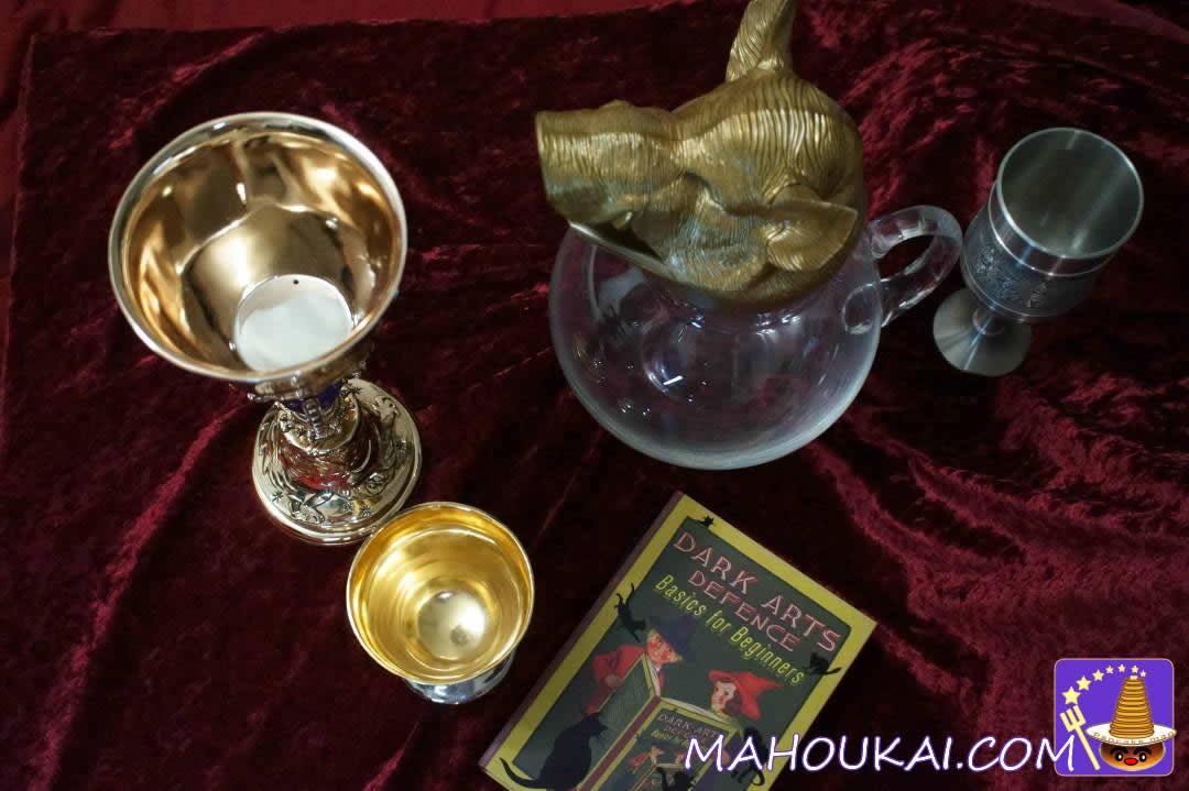 ホグワーツの金色ゴブレット、ピッチャー、ダンブルドアのカップとD.A.D.A.教科書(minalima)