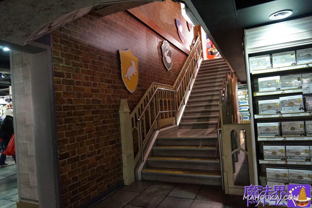 日本でいう1階のグランドフロアから地下1階へ降りる 階段の壁はレンガ調でホグワーツ四寮のシンボル